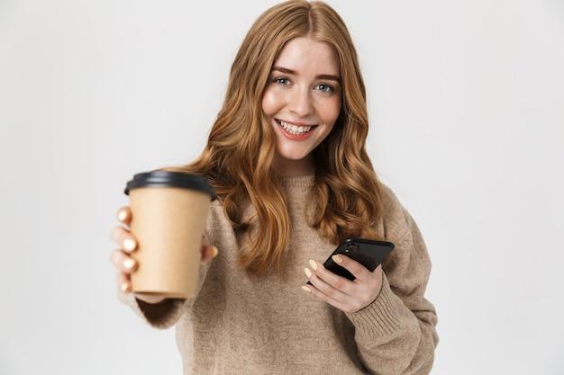Aantrekkelijk jong meisje met een trui die over een witte muur staat en afhaalkoffie drinkt tijdens het gebruik van een mobiele telefoon
