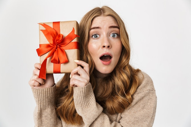 Aantrekkelijk jong meisje met een trui die over een witte muur staat en een geschenkdoos toont