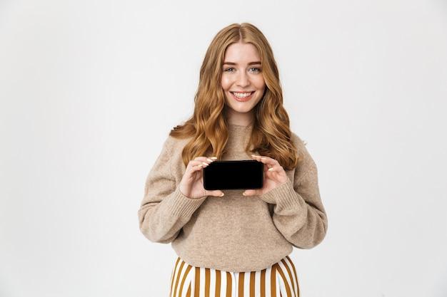 Aantrekkelijk jong meisje met een trui die over een witte muur staat en een mobiele telefoon met een leeg scherm toont