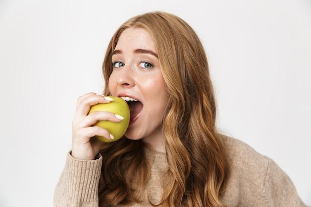 Aantrekkelijk jong meisje met een trui die over een witte muur staat en groene appel eet