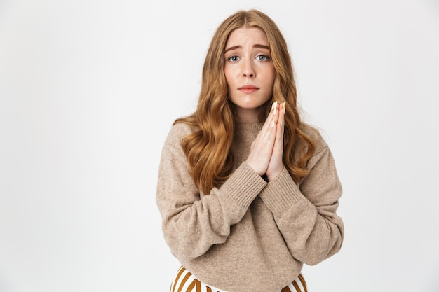 Aantrekkelijk jong meisje met een trui die over een witte muur staat en om iets vraagt