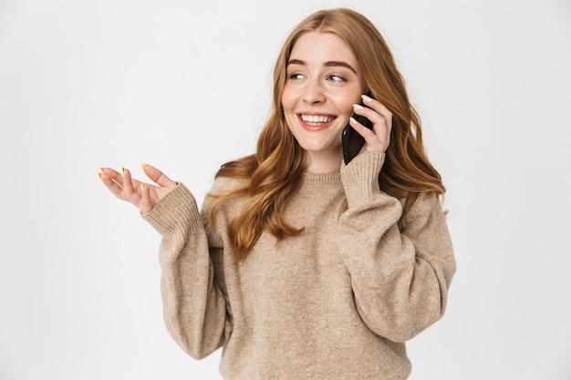 Aantrekkelijk jong meisje met een trui die over een witte muur staat en op een mobiele telefoon praat