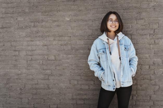 Aantrekkelijk jong meisje met kort haar, bril en street style kleding, leunend op een bakstenen muur.