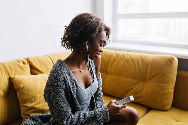Aantrekkelijk jong meisje met kort krullend haar luisteren muziek in oortelefoons, met telefoon in de hand, zittend op gele sofa met kussens, thuis rusten