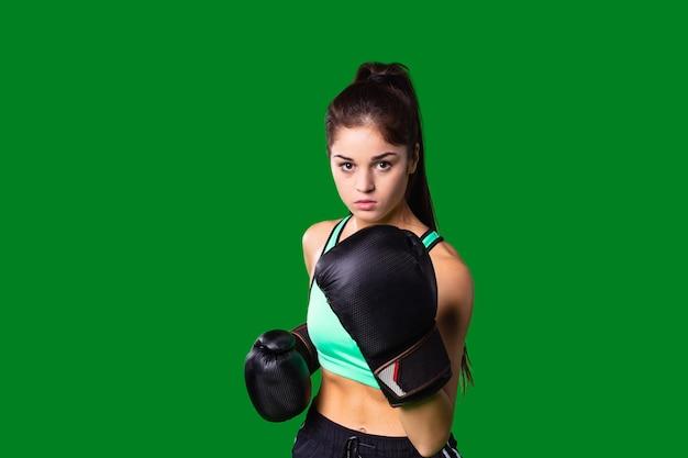 Aantrekkelijk jong meisje met slank lichaam dat sportkleding en bokshandschoenen draagt, traint in de training...