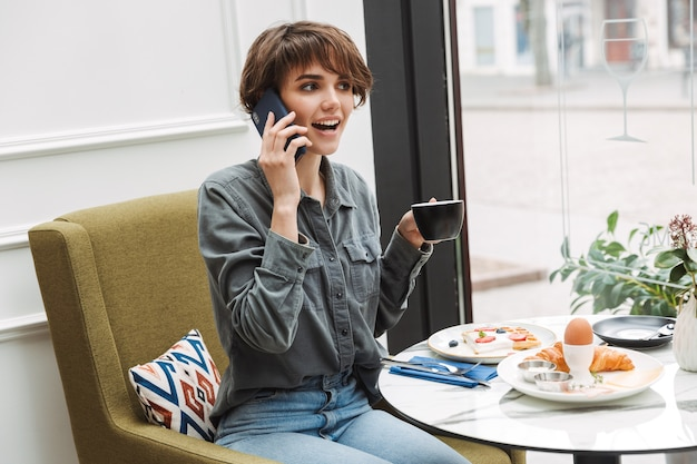 Aantrekkelijk jong meisje ontbijten in het café binnenshuis, praten op mobiele telefoon