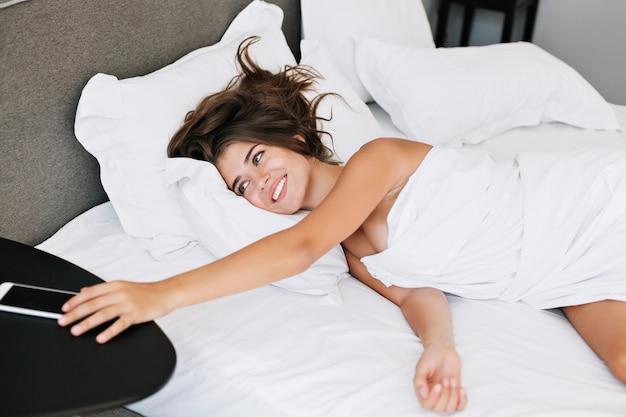 Aantrekkelijk jong meisje op bed in modern appartement in de ochtend. ze pakt handig op tafel en glimlacht.
