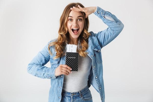 Aantrekkelijk jong meisje permanent geïsoleerd over wit, paspoort met vliegtickets tonen, vieren
