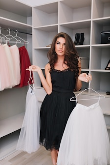 Aantrekkelijk jong meisje staat in de kleedkamer en kan geen keuze maken tussen twee rokken, ze kijkt bedachtzaam opzij. ze is gekleed in een zwarte jurk. echte emoties
