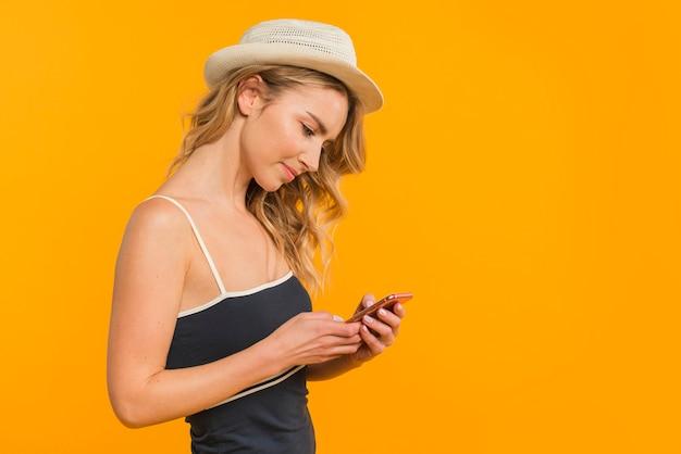 Aantrekkelijk jong model dat mobiele telefoon met behulp van