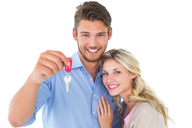 Aantrekkelijk jong paar dat nieuw huissleutel toont