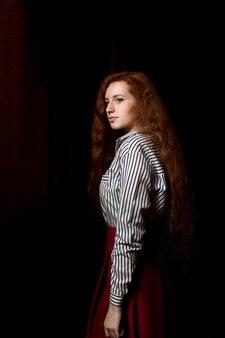 Aantrekkelijk jong roodharig model dat wit gestreept overhemd en rode rok draagt. vrouw poseren in een donkere kamer