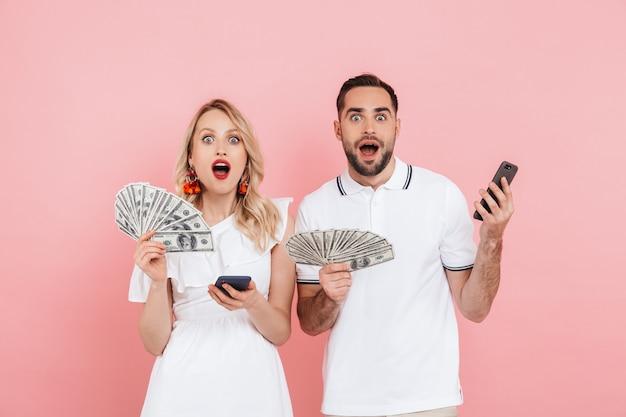 Aantrekkelijk jong stel dat samen staat geïsoleerd over roze, geldbankbiljetten toont, met behulp van mobiele telefoon