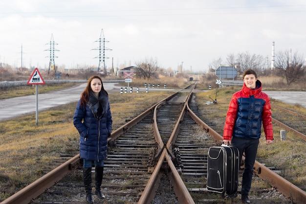 Aantrekkelijk jong stel in modieuze warme kleding die op een spoorlijn staat te wachten tot de trein arriveert met een ingepakte koffer