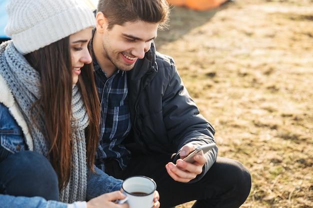 Aantrekkelijk jong stel rust terwijl ze buiten in de tent zitten, beker en thermos vasthouden, mobiele telefoon gebruiken using