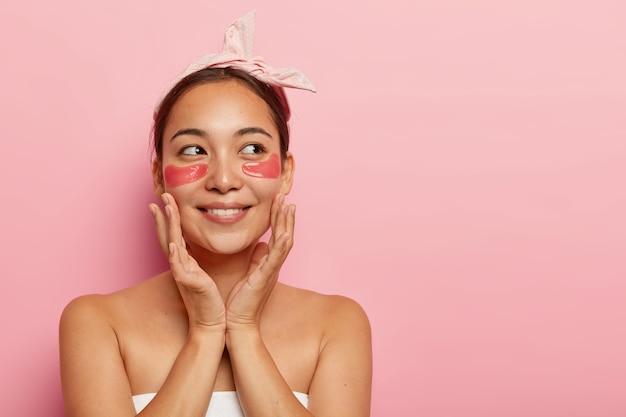 Aantrekkelijk jong vrouwelijk model raakt gezicht, geniet van frisheid van de huid, past anti-verouderingspatches onder de ogen toe, glimlacht zachtjes, kijkt opzij aan de rechterkant, draagt boog hoofdband, vermindert zwelling en rimpels