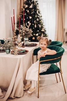 Aantrekkelijk kaukasisch meisje in een mooie jurk in de keuken in de buurt van de kerstboom en glimlacht