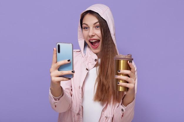 Aantrekkelijk kaukasisch meisje selfie maken tegen lila achtergrond, opgewonden, mond wijd open houden, genieten van warme drank, bleke roze regenjas dragen.
