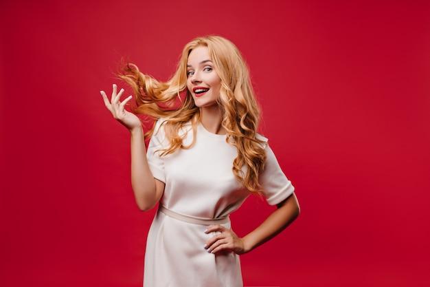 Aantrekkelijk kaukasisch meisje speelt met haar lange haren op rode muur. indoor foto van aantrekkelijke stijlvolle vrouw in jurk.