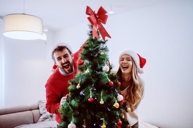 Aantrekkelijk kaukasisch paar met santahoeden op hoofden die met verfraaide kerstmisboom stellen terwijl status in woonkamer.