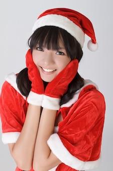 Aantrekkelijk kerstmismeisje met gelukkige uitdrukking, close-upportret over grijze muur.