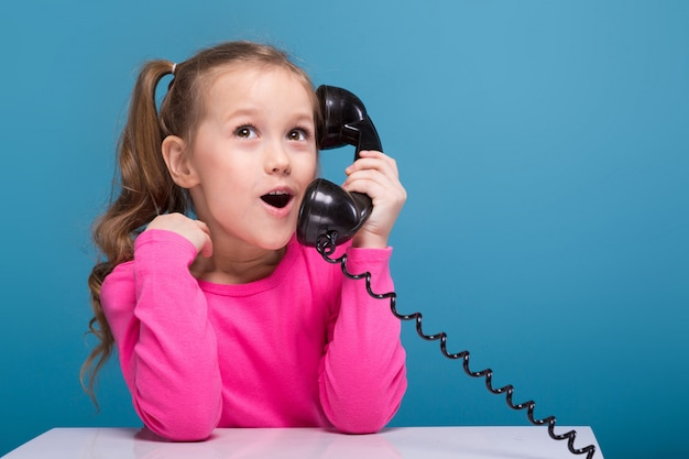 Aantrekkelijk klein schattig meisje in roze shirt met aap en blauwe broek houden lege poster en praat een telefoon