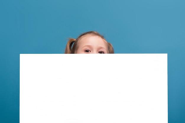 Aantrekkelijk klein schattig meisje in roze shirt met aap en blauwe broek houden lege poster