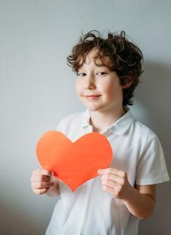 Aantrekkelijk krullend haar tween jongen met rood hart op grijze achtergrond, moederdag