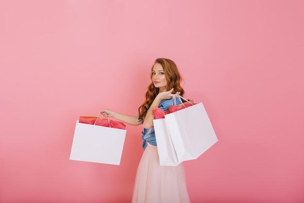 Aantrekkelijk krullend meisje dat in denimoverhemd grote witte zakken van kledingwinkel houdt die op roze achtergrond wordt geïsoleerd. charmante langharige jonge vrouw in schattige outfit poseren met pakketten na het winkelen.