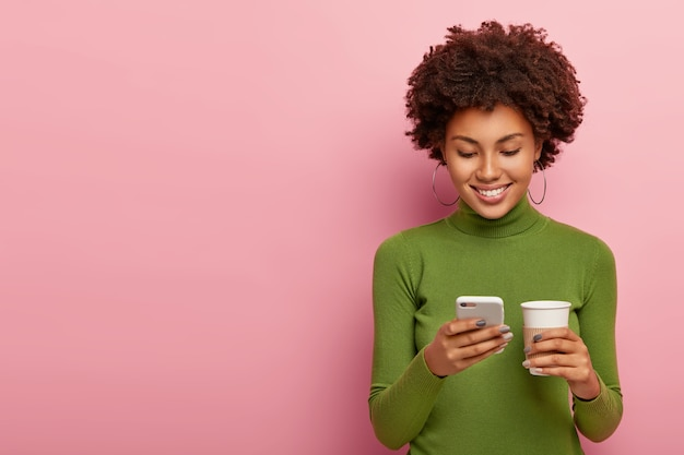 Aantrekkelijk lachend meisje creëert online post, houdt moderne mobiele telefoons in, controleert e-mailbox, bladert op internet