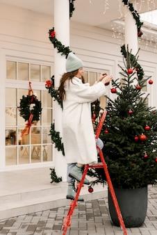 Aantrekkelijk lachend meisje siert een kerstboom in de buurt van het huis