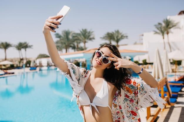 Aantrekkelijk lachende meisje met plezier op resort en selfie maken op zuidelijk landschap met exotische palmbomen. slanke gelooide jonge dame in witte bikini die foto van zichzelf neemt die vredesteken toont