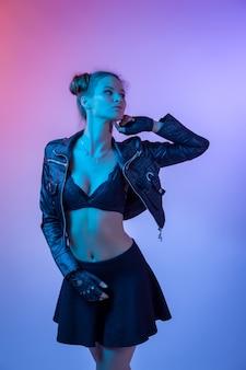 Aantrekkelijk langharig meisje, stijlvolle mode. creatief kleurrijk neonportret. mooi meisje een zwart lederen jas, ondergoed en shirt poseren. filmisch nachtportret van vrouw in neon.