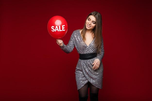 Aantrekkelijk langharige blanke meisje toont ballon met tekstverkoop op rode achtergrond