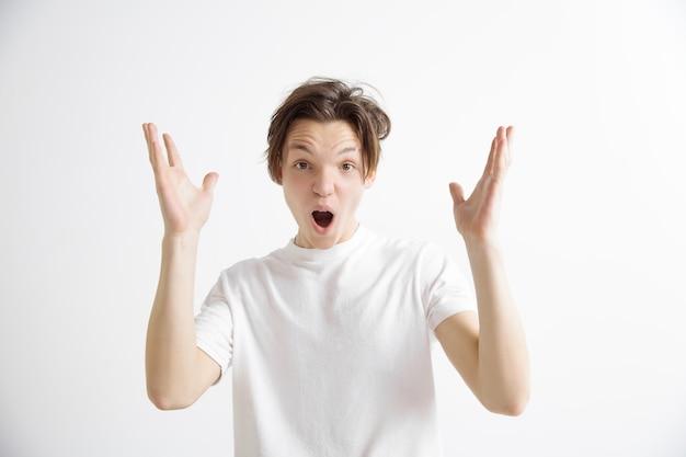 Aantrekkelijk mannelijk half-lengte voorportret op grijze studieachtergrond. jonge emotionele verrast man die met open mond. menselijke emoties, gezichtsuitdrukking concept