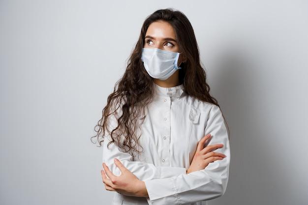 Aantrekkelijk meisje arts in medische mantel. jonge vrouw die op witte achtergrond glimlacht. advertentie voor medische kliniek en blogs.