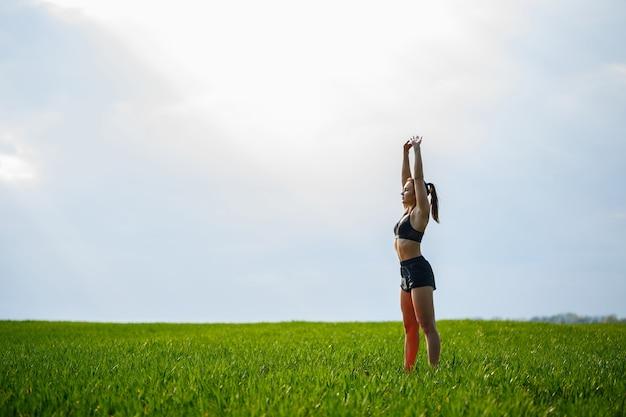 Aantrekkelijk meisje atleet warming-up buitenshuis, oefeningen voor spieren. jonge vrouw gaat voor sport, gezonde levensstijl, atletisch lichaam. ze is in sportkleding, zwarte top en korte broek