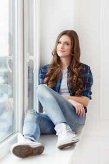 Aantrekkelijk meisje bij het raam