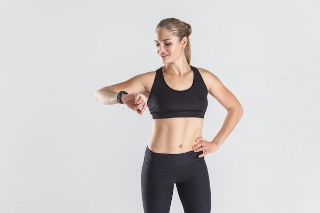 Aantrekkelijk meisje dat fitnesstracker bekijkt en calorieën verliest