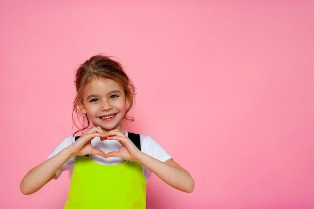 Aantrekkelijk meisje dat hartteken toont en op de roze muur glimlacht