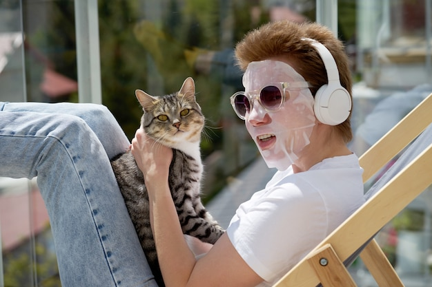 Aantrekkelijk meisje dat met modieus kapsel gezichtsmasker op gezicht toepast, met kat speelt en aan muziek luistert.