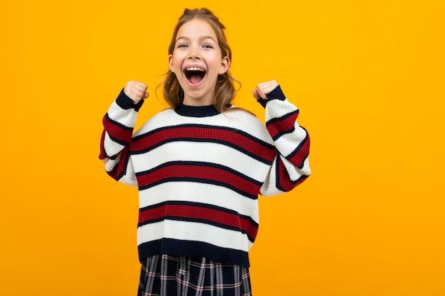 Aantrekkelijk meisje dat met wijd open mond nieuws op een gele studioachtergrond schreeuwt met exemplaarruimte.