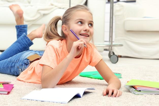 Aantrekkelijk meisje dat op de vloer ligt en in voorbeeldenboek schrijft