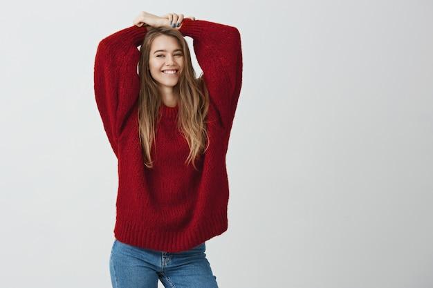 Aantrekkelijk meisje dat pret zoekt. portret van slanke blanke vrouw in trendy trui hand in hand boven het hoofd, breed glimlachend en poseren voor de camera, in een goed humeur.