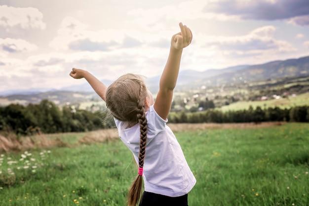 Aantrekkelijk meisje dat zich uitstrekt en geeuwen op de top van de bergen in de ochtend, zomerse natuur, gezonde levensstijl, buiten
