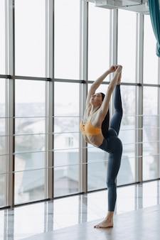 Aantrekkelijk meisje doet fitness oefeningen met yoga op de vloer tegen het oppervlak van panoramische ramen