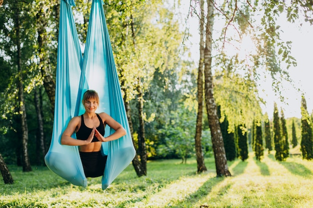 Aantrekkelijk meisje doet vlieg yoga gesloten ogen buitenshuis. gebaar namaste