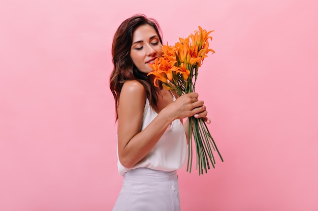 Aantrekkelijk meisje geniet van de geur van bloemen op geïsoleerde achtergrond