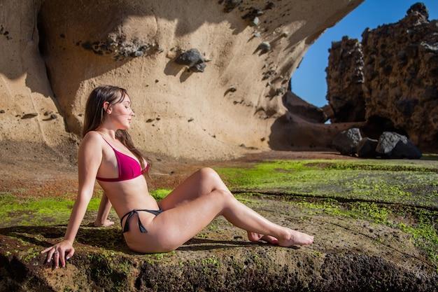 Aantrekkelijk meisje in bikini ontspant en zonnebaadt op een rots.