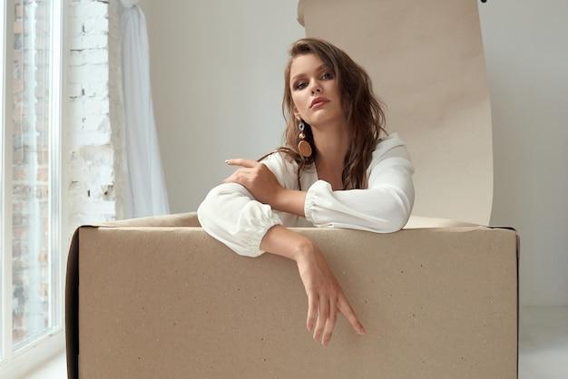 Aantrekkelijk meisje in blouse en trendy oorbellen in studio